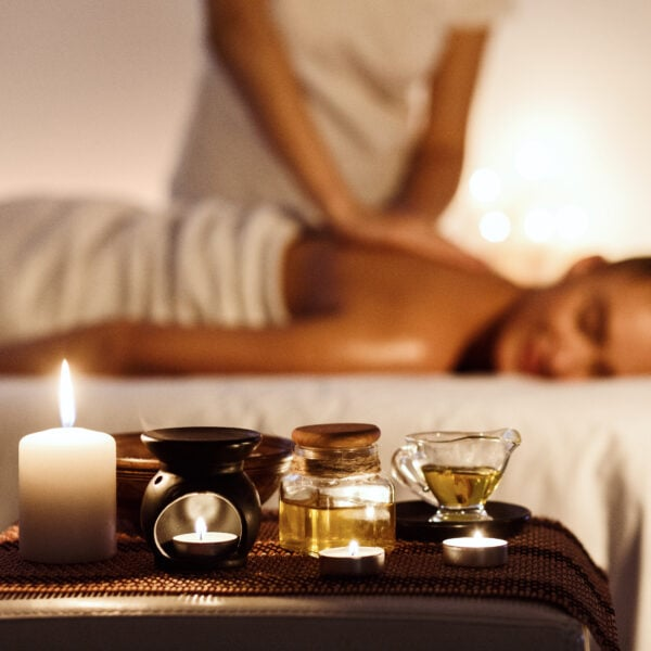 Aroma spa. Woman enjoying massage in luxury spa with candle on foreground